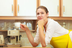 Mature woman holding cup of coffee in kitchen. Royalty Free Stock Images