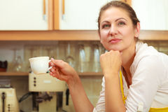 Mature woman holding cup of coffee in kitchen. Stock Image