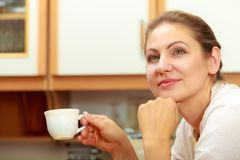 Mature woman holding cup of coffee in kitchen. Royalty Free Stock Photography