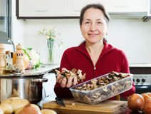Mature woman holding dried mushrooms Royalty Free Stock Images