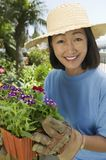 Mature Woman Holding Flower Pot Stock Image