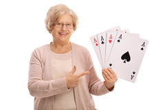 Mature woman holding four aces and pointing Royalty Free Stock Images