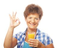 Mature woman holding a glass of orange juice Royalty Free Stock Photo