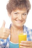 Mature woman holding a glass of orange juice Royalty Free Stock Photos