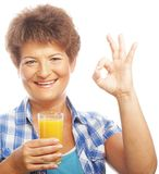 Mature woman holding a glass of orange juice Royalty Free Stock Image