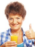Mature woman holding a glass of orange juice Stock Photos