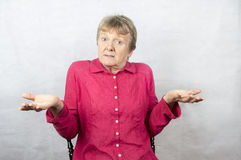 Mature woman holding hands out with a confused expression. Stock Photos