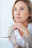 Mature woman holding her glasses daydreaming Royalty Free Stock Photography