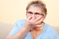 Mature woman holding her nose Royalty Free Stock Image
