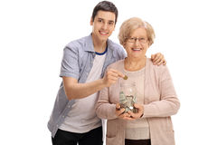 Mature woman holding jar with man putting coin in it Stock Photo