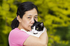 Mature woman holding large family cat outdoors Stock Image