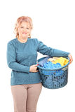 Mature woman holding a laundry basket Royalty Free Stock Photography