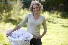 A mature woman holding a laundry basket outside Royalty Free Stock Images