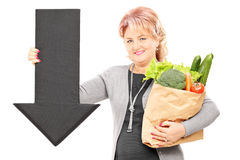 Mature woman holding a paper bag full of groceries and big black. Arrow pointing down isolated on white background Stock Photos