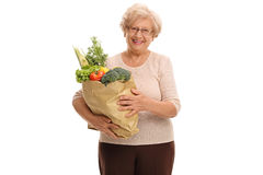 Mature woman holding a paper bag full of groceries. Happy mature woman holding a paper bag full of groceries isolated on white background Royalty Free Stock Photos