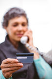 Mature woman holding payment card while talking on telephone Royalty Free Stock Photos