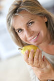 Mature woman holding pear stock image