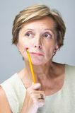 Mature woman holding pencil. Woman in her fifties holds pencil, portrait, close-up Stock Photography