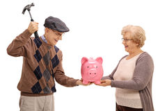 Mature woman holding a piggybank while a man is preparing to break it. Mature women holding a piggybank while a mature men is preparing to break it with a hammer Royalty Free Stock Photos