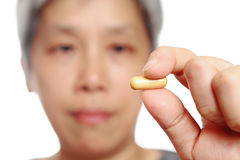Mature woman holding pill Stock Photo