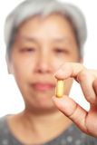 Mature woman holding pill Royalty Free Stock Photo