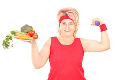 Mature woman holding plate of vegetables and a dumbbell. Isolated on white background royalty free stock images