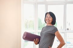 Mature woman holding rolled up exercise mat at gym. Cheerful female fitness instructor holding mat royalty free stock photos