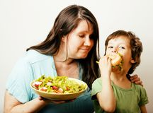 Mature woman holding salad and little cute boy with hamburger te Stock Photo