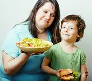 Mature woman holding salad and little cute boy with hamburger teasing close up, family food royalty free stock photo