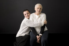 Mature woman holding senior woman in her arms Stock Image