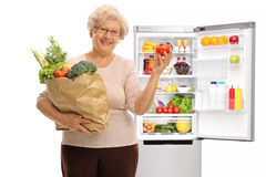 Mature woman holding shopping bag filled with vegetables and tom Stock Images