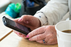 Elderly woman using smartphone. Mature well groomed woman in coffee shop cafe holding mobile phone in hands Royalty Free Stock Images