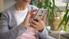 Mature woman is holding smartphone, listening music stock video footage