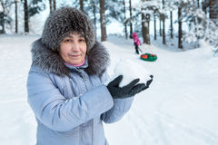 Mature woman holding snow in hands while standing in tube downhill in forest Stock Images