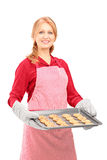 Mature woman holding a tray with baked cookies Royalty Free Stock Images
