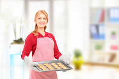 Mature woman holding a tray with baked cookies and posing at hom Royalty Free Stock Photo