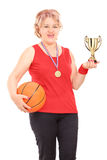 Mature woman holding trophy and a basketball Stock Photos