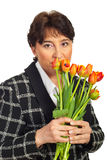 Mature woman holding tulips in front of face Royalty Free Stock Images