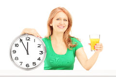 Mature woman holding a wall clock and glass of orange juice Stock Photos