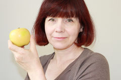 Mature Woman Holds an Apple Stock Images
