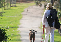 Mature woman on holiday walking pet dog. A nostalgic type portrait of a middle-aged woman taking her pet dog for a relaxing walk on a leash while on an enjoyable Royalty Free Stock Image