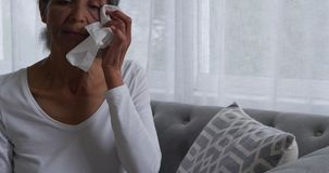Mature woman at home. Front view close up of a mature mixed race woman crying and wiping her eyes with a tissue stock video footage