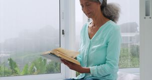 Mature woman at home. Front view close up of a mature mixed race woman reading a book at home stock video footage