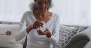 Mature woman at home. Front view close up of a mature mixed race woman undoing a bottle of tablets at home stock footage