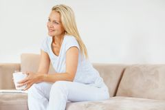 Mature woman at home holding a cup in thought Royalty Free Stock Photos
