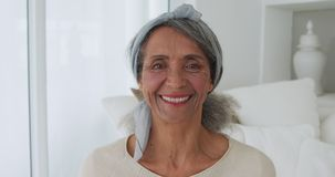 Mature woman at home. Portrait close up of a mature mixed race woman smiling to camera at home stock video