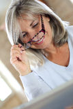 Mature woman at home removing eyeglasses Royalty Free Stock Photos