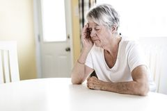 Mature woman at home touching her head with her hands while having a headache pain Stock Photo