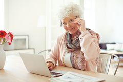 Mature Woman at Home Using Laptop Royalty Free Stock Photography