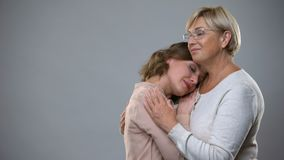 Mature woman hugging adult daughter on grey background, motherhood support. Stock footage stock video footage